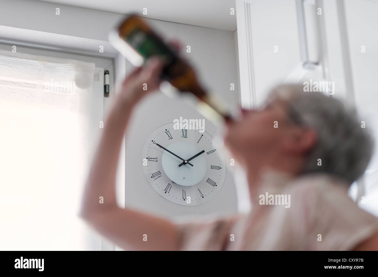 Alcohol-dependent woman, alcoholic, drinking a bottle of beer in broad daylight - Stock Image