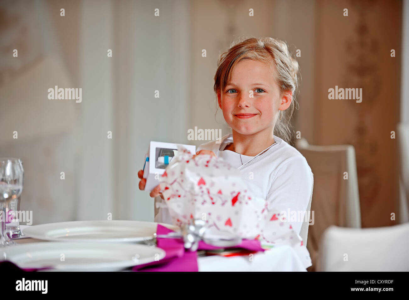Girl, 9 years, holding present, on her First Communion day, Muensterland region, North Rhine-Westphalia - Stock Image