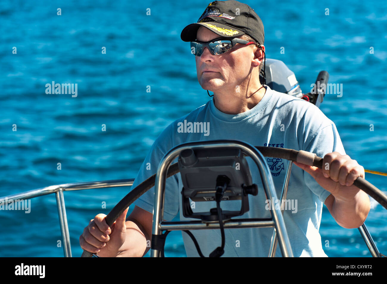 Skipper at the helm of his sailing yacht Stock Photo