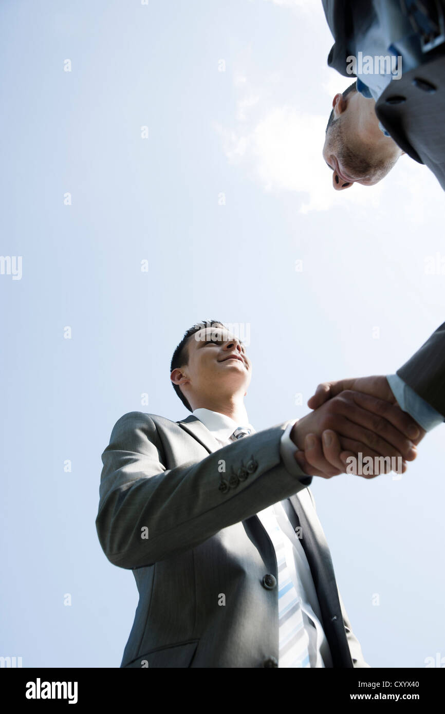 Two businessmen greeting each other with a handshake - Stock Image