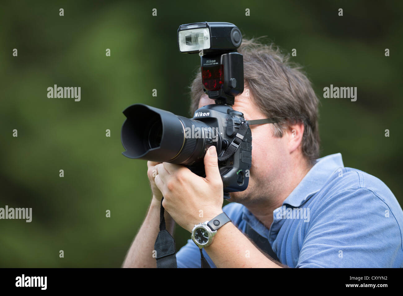 Photographer, mid 40's, taking pictures, looking through the viewfinder of a Nikon D4 digital SLR camera with - Stock Image