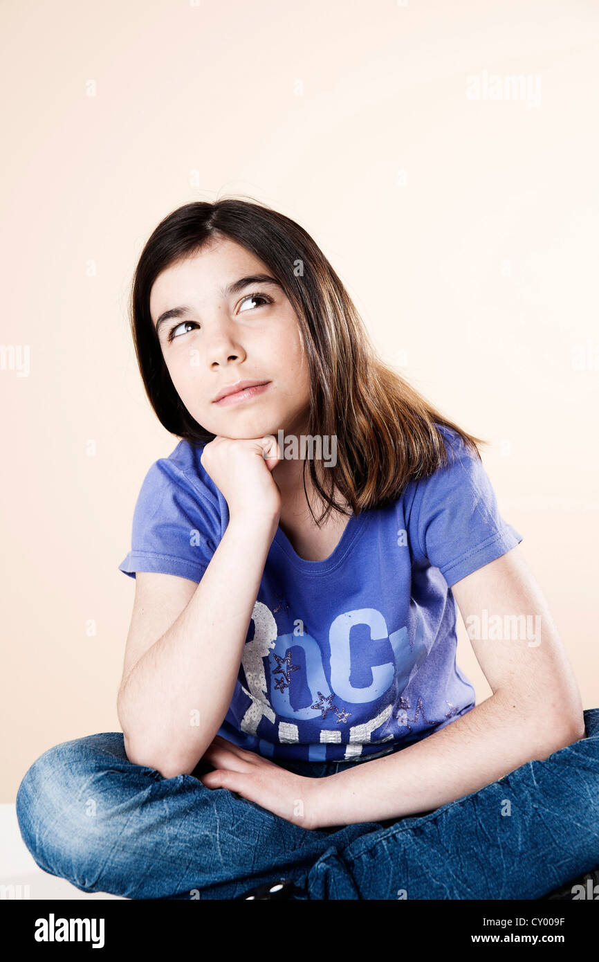Girl sitting and thinking with her legs crossed - Stock Image