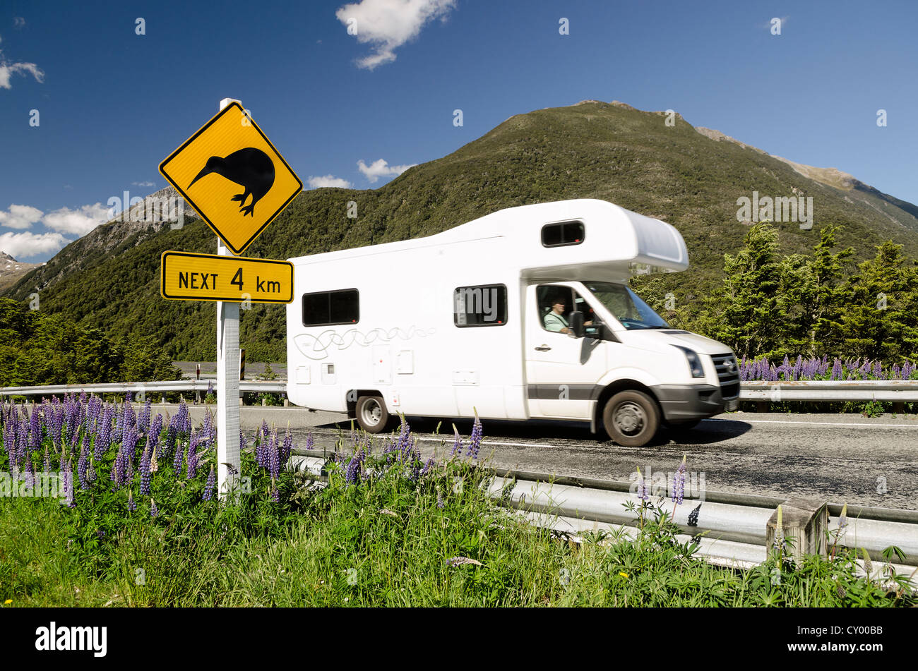 Campervan driving past a warning sign on a highway, 'Kiwis next 4 km', Porters Pass, Craigieburn Range, - Stock Image