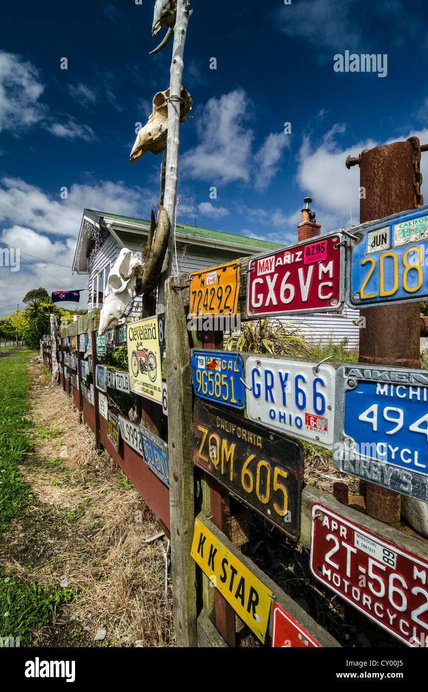 Many U.S. license plates and skulls on a wooden fence, South Island, New Zealand - Stock Image