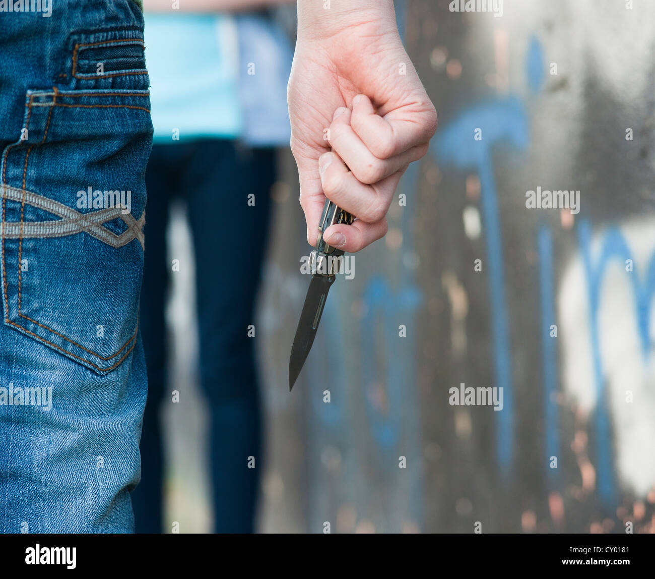 Boy threatening a girl with a knife - Stock Image