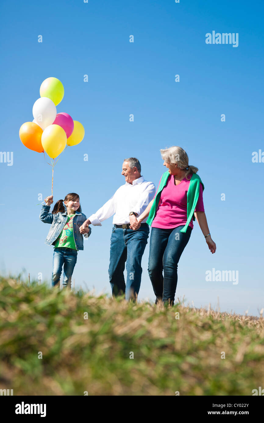 Girls holding balloons in her hand while walking with her grandparents across a meadow Stock Photo