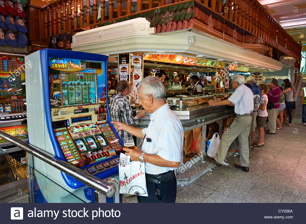 Man playing a slot machine in a Restaurant Bar in Madrid Spain Stock Photo