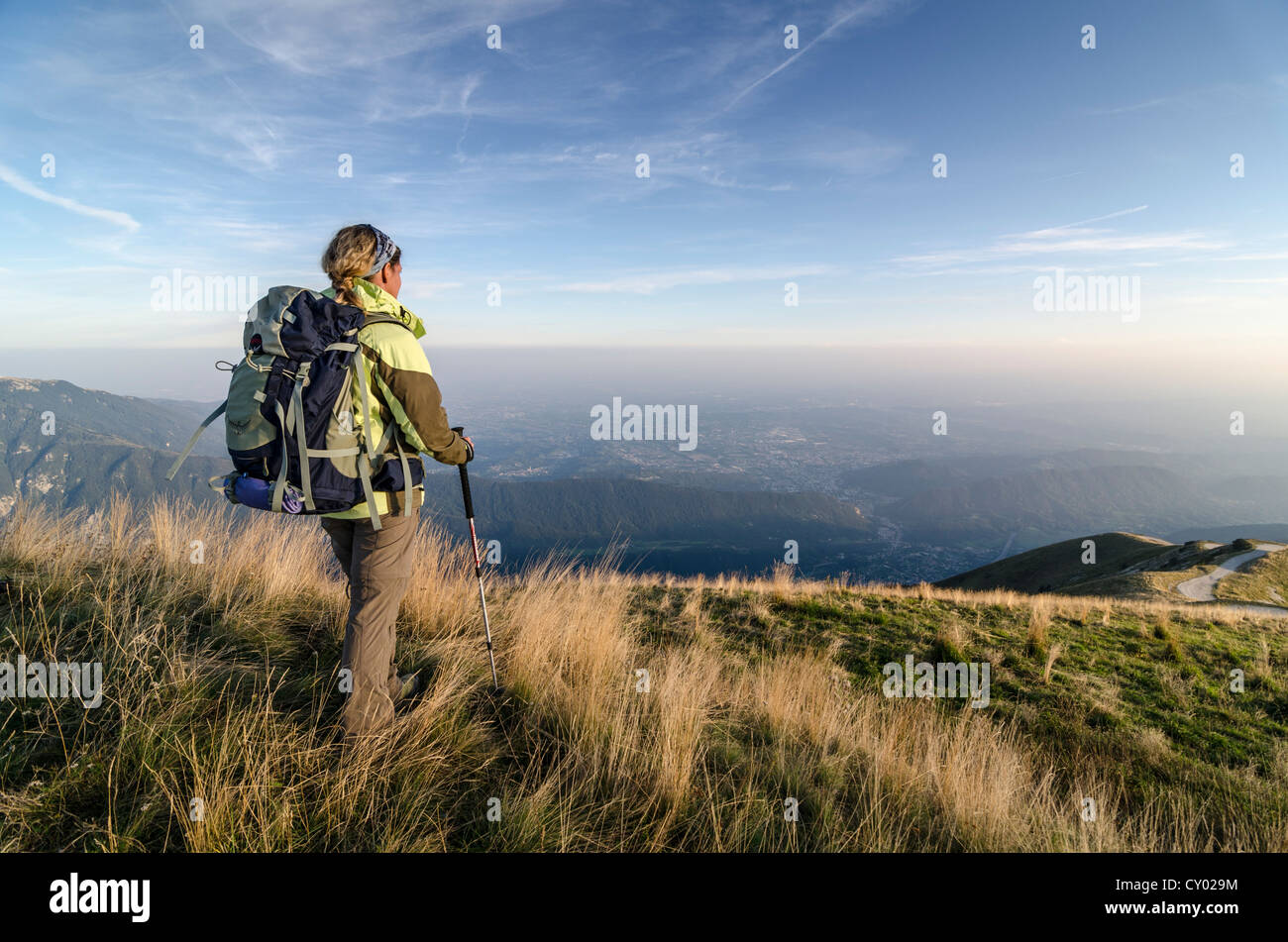 Female hiker carrying a backpack, view of the vast plain of the Piave river as seen from Col Visentin mountain, - Stock Image