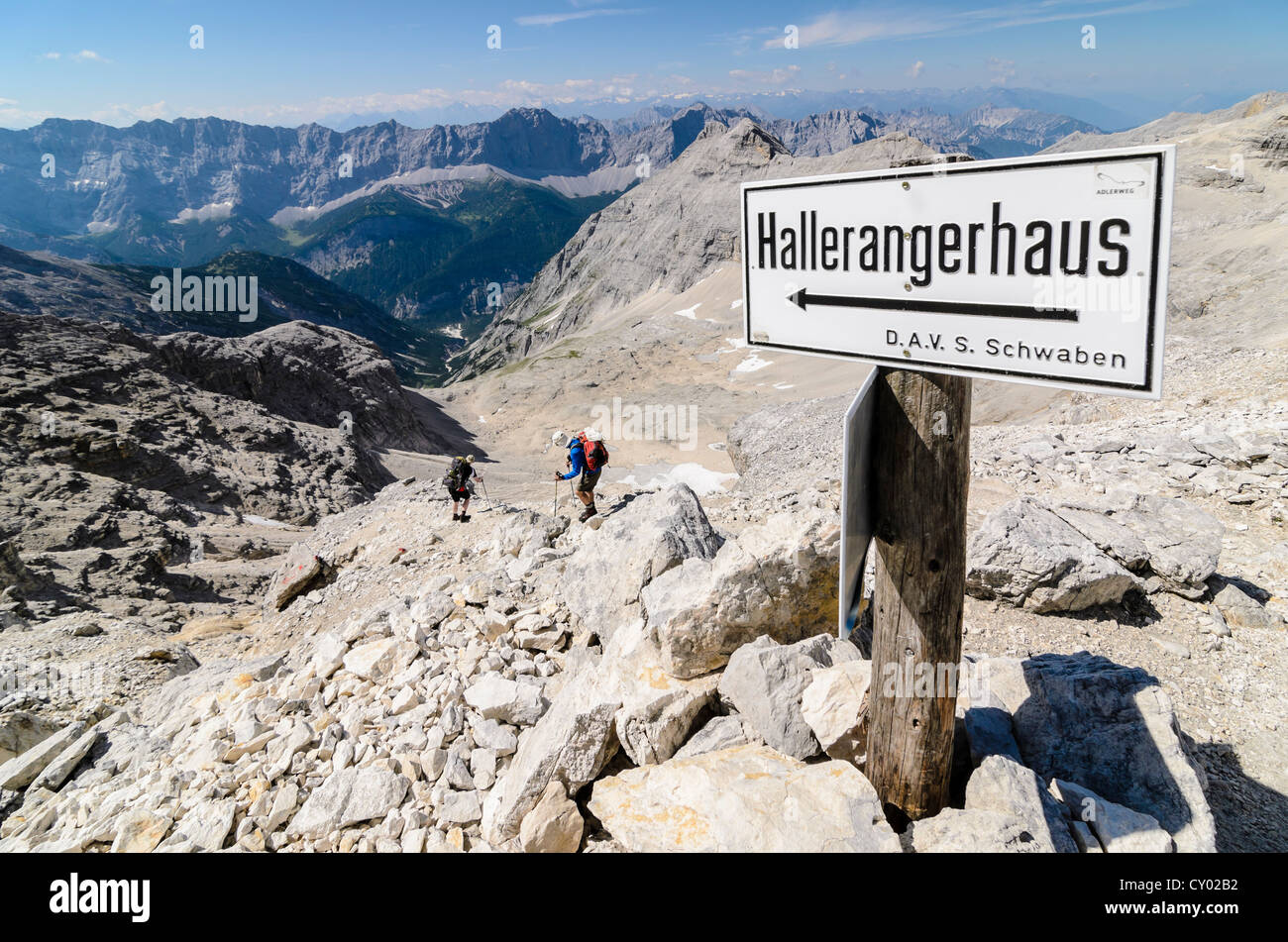 Signpost for Hallerangerhaus with two hikers, descent from Mt Schlauchkar, Karwendel Mountains National Park, Tyrol, - Stock Image