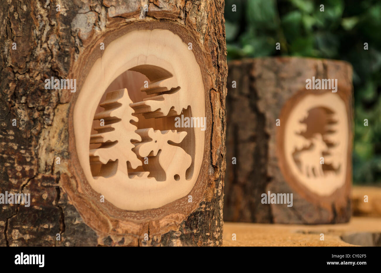 Carvings out of a piece of tree trunk with bark - Stock Image