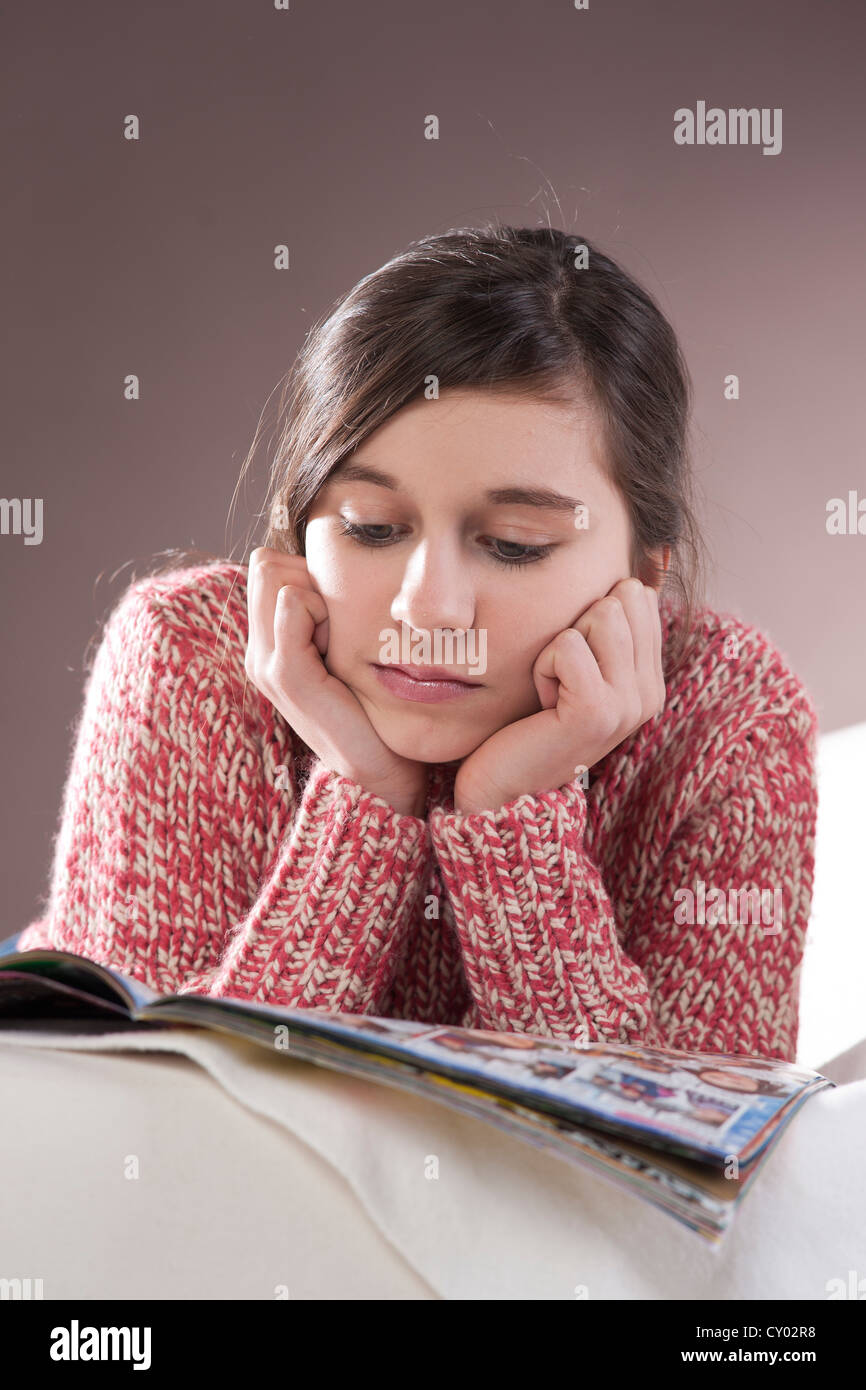 Girl lying on a couch and reading a magazine - Stock Image