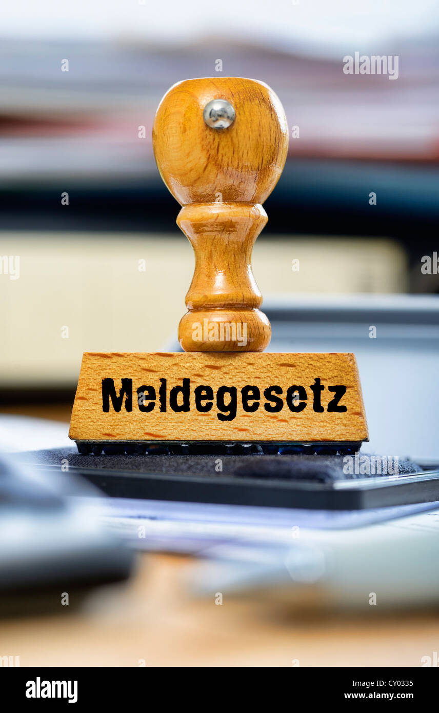 Rubber stamp with the wording 'Meldegesetz', German for registration law, on a desk - Stock Image