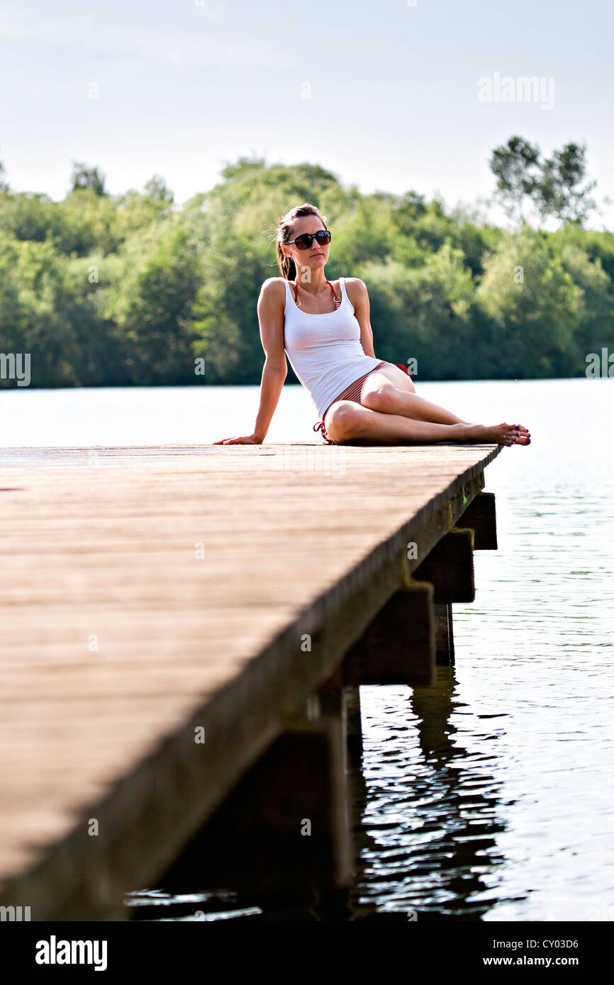 Young woman sitting on jetty at lakeside - Stock Image