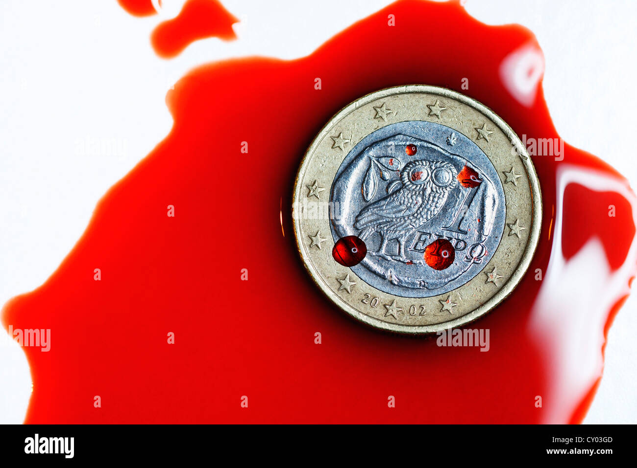 Greek euro in a pool of blood, symbolic image for the debt crisis in Greece - Stock Image