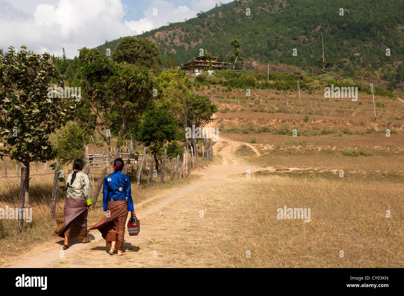 Two women in national dress on the way to the Chimi Lhakhang fertility temple, Lobesa, Bhutan, South Asia - Stock Image