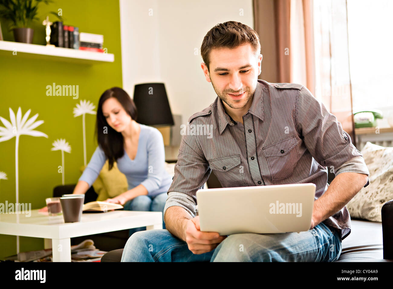 Young man at home, with a laptop, young woman at back - Stock Image