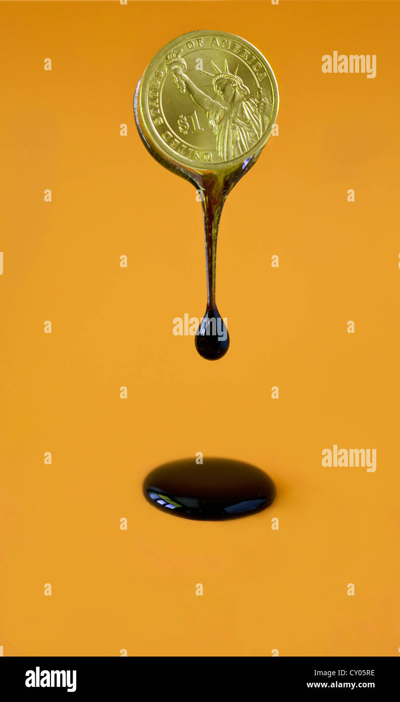 oil bleeding from US dollar coin - Stock Image