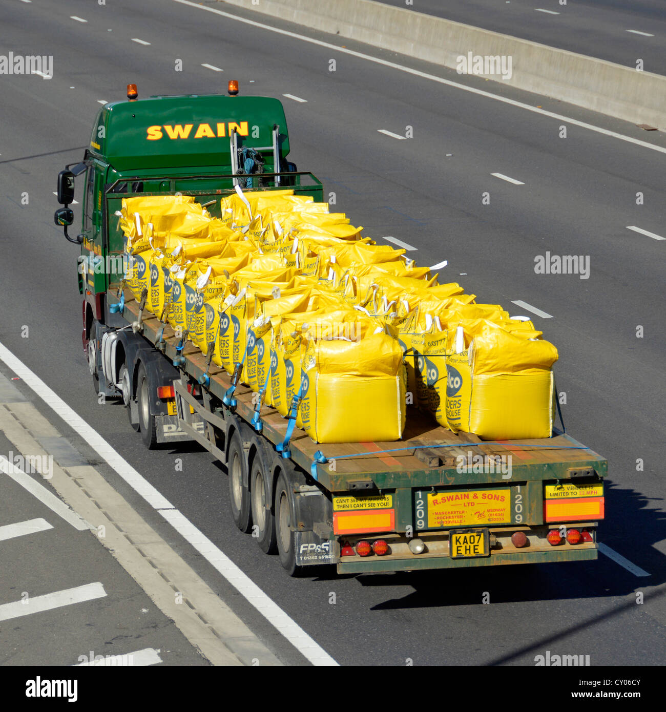 Articulated lorry on motorway loaded with large bags of loose bulk materials - Stock Image