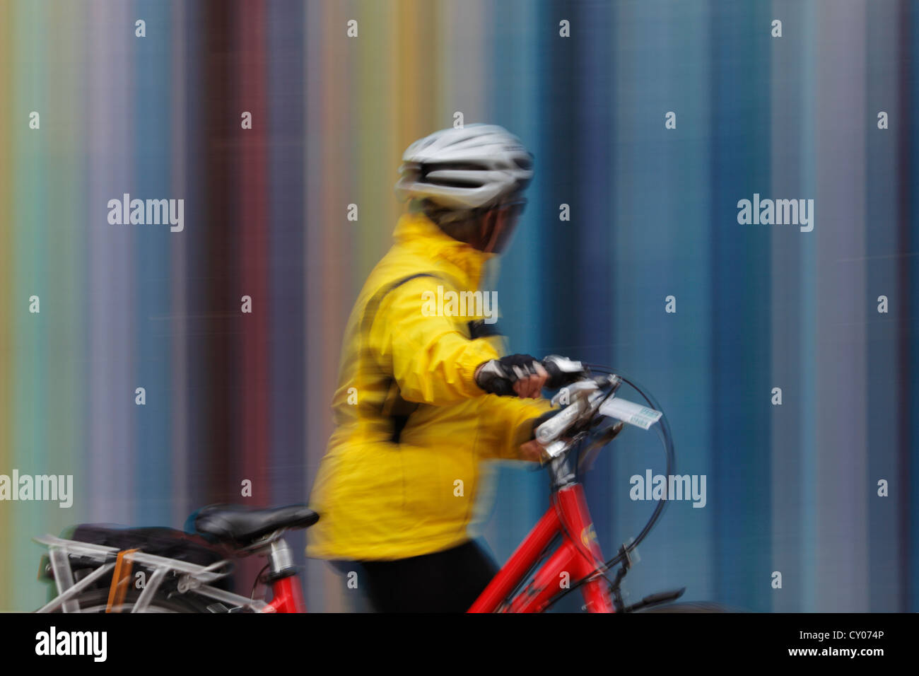 A female tourist with bike passing the Tour Moretti at the Esplanade du General de Gaulle in La Defense, Paris - Stock Image