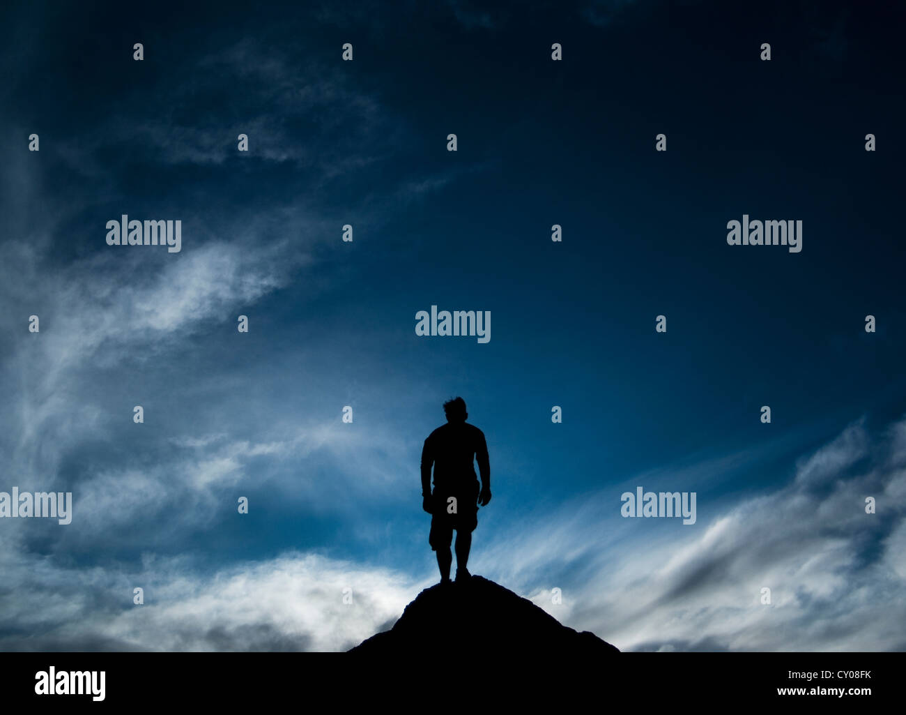 Silhouette of male figure standing on rock - Stock Image