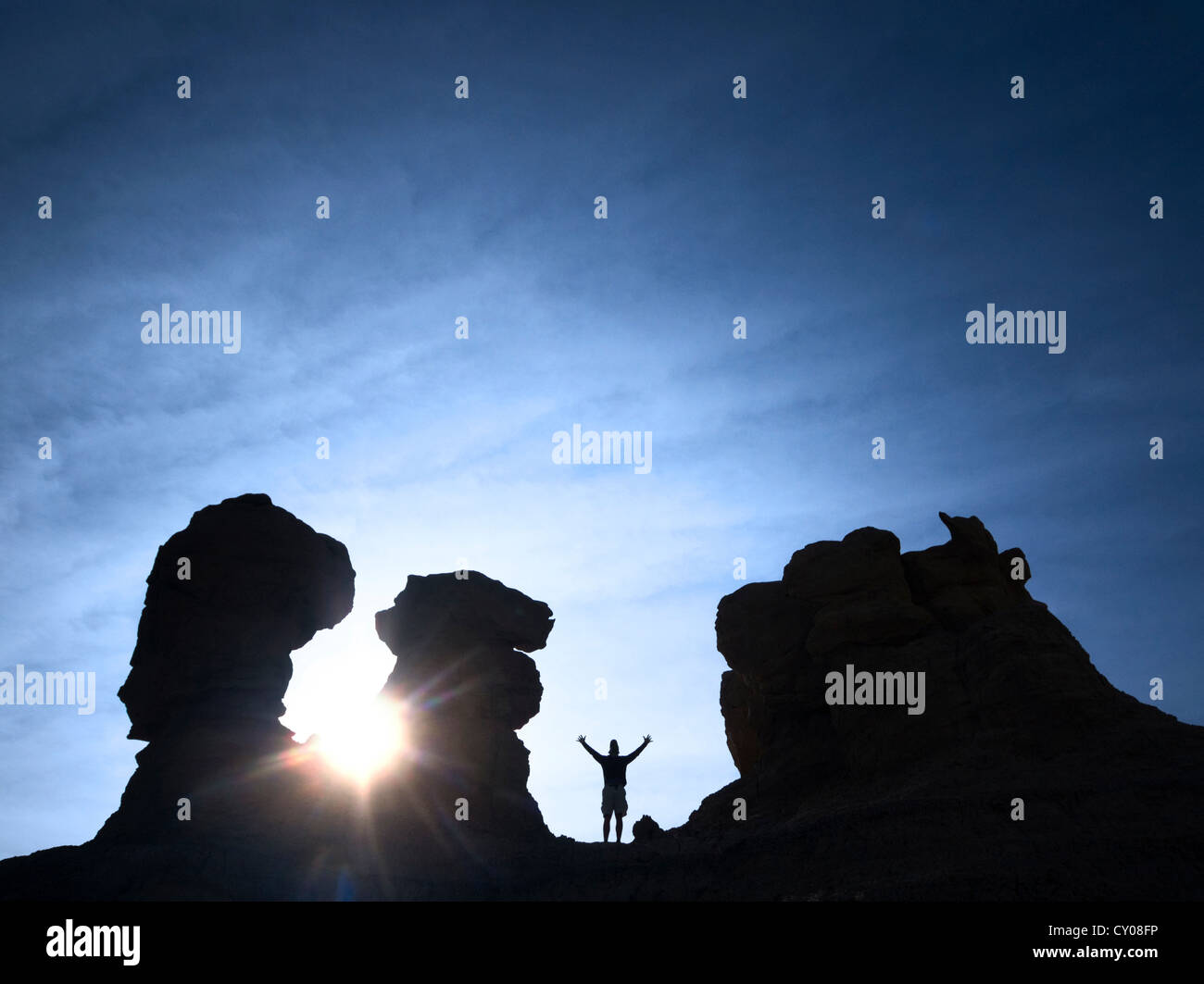 Silhouette of male figure standing on rock and sunrise - Stock Image