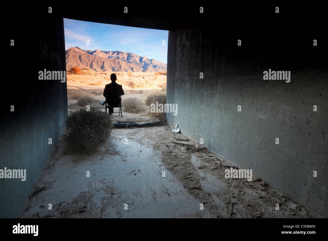Silhouette of male figure sitting in tunnel in desert - Stock Image