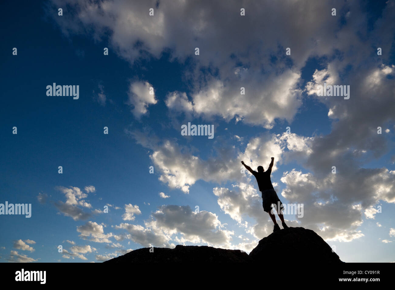 Silhouette of male figure standing on rock in celebration with arms raised - Stock Image