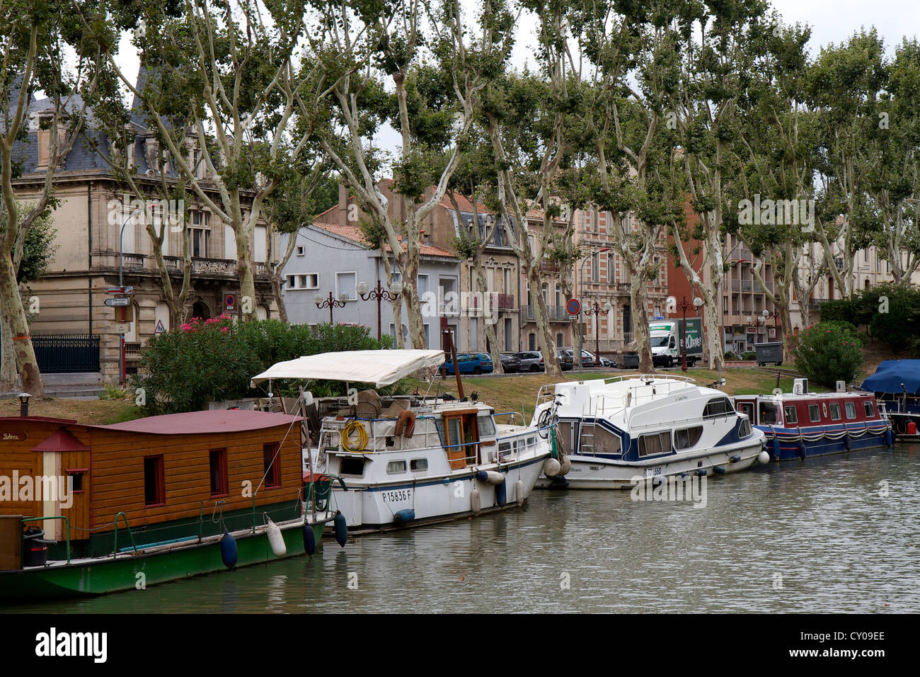 Canal side house boats and barges in Narbonne on the Canal de la Robine in Southern France.  The canal is lined Stock Photo