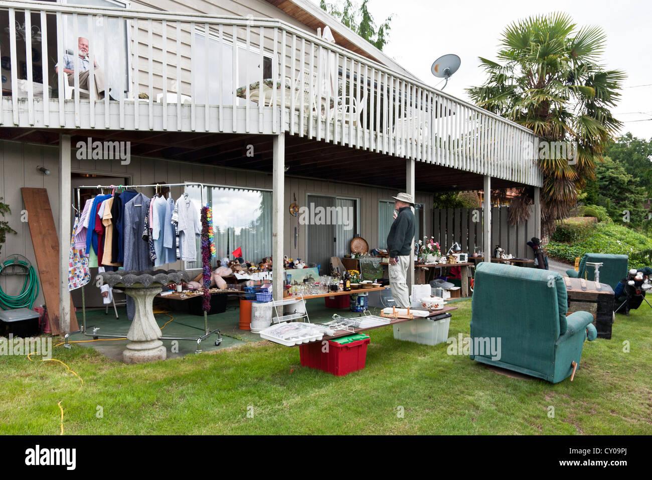 Senior Man Checks Out Display Of Furniture Bric A Brac Kitsch At Yard  Garage Sale On Lawn Neat Suburban House Edmonds Washington