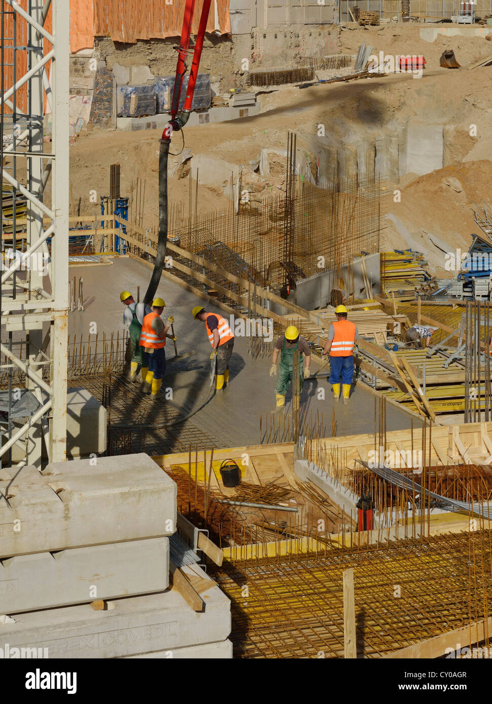 Large construction site, workers pouring concrete into an area surrounded by boarding and reinforcements, North - Stock Image