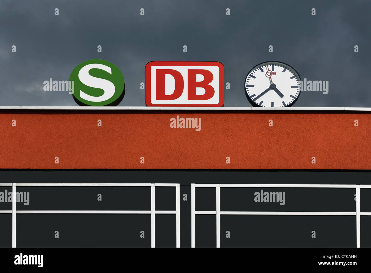 Logos of the S-Bahn commuter railway and the Deutsche Bahn federal railway beside a clock, combined public transport Stock Photo