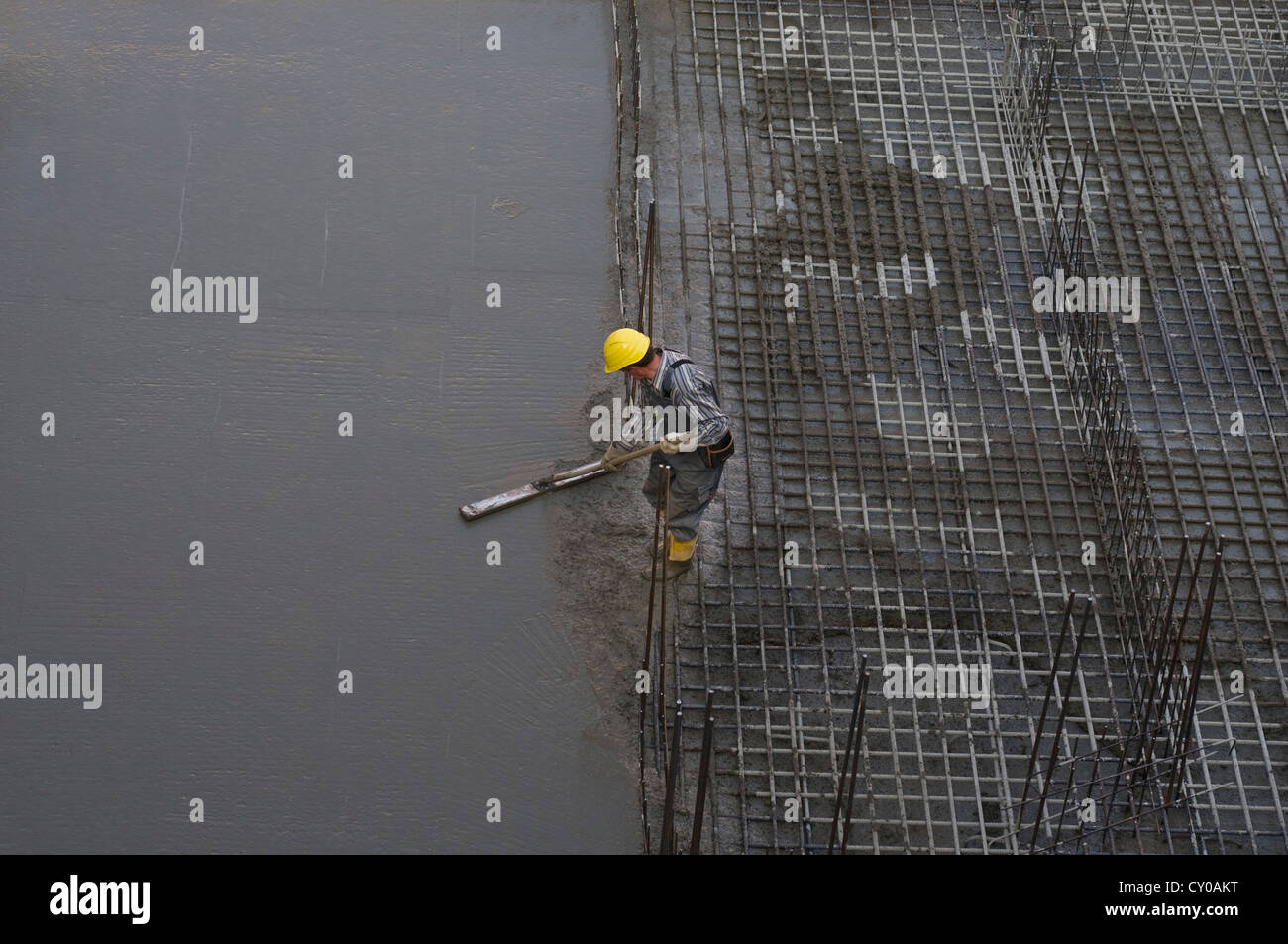 Construction worker levelling fresh concrete on reinforcement, PublicGround - Stock Image