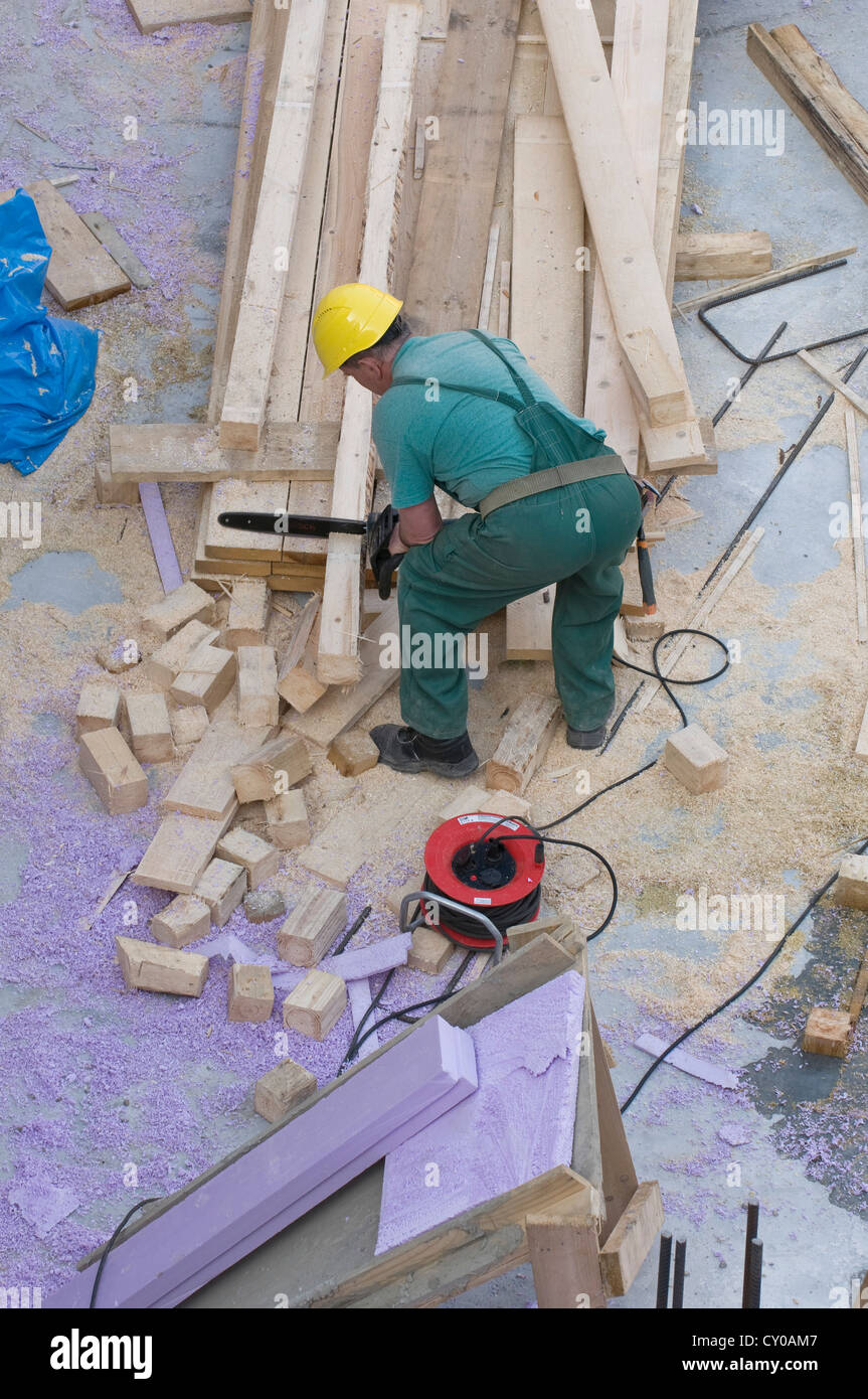 Construction worker cutting beams with a chainsaw, bird's eye perspective, PublicGround - Stock Image