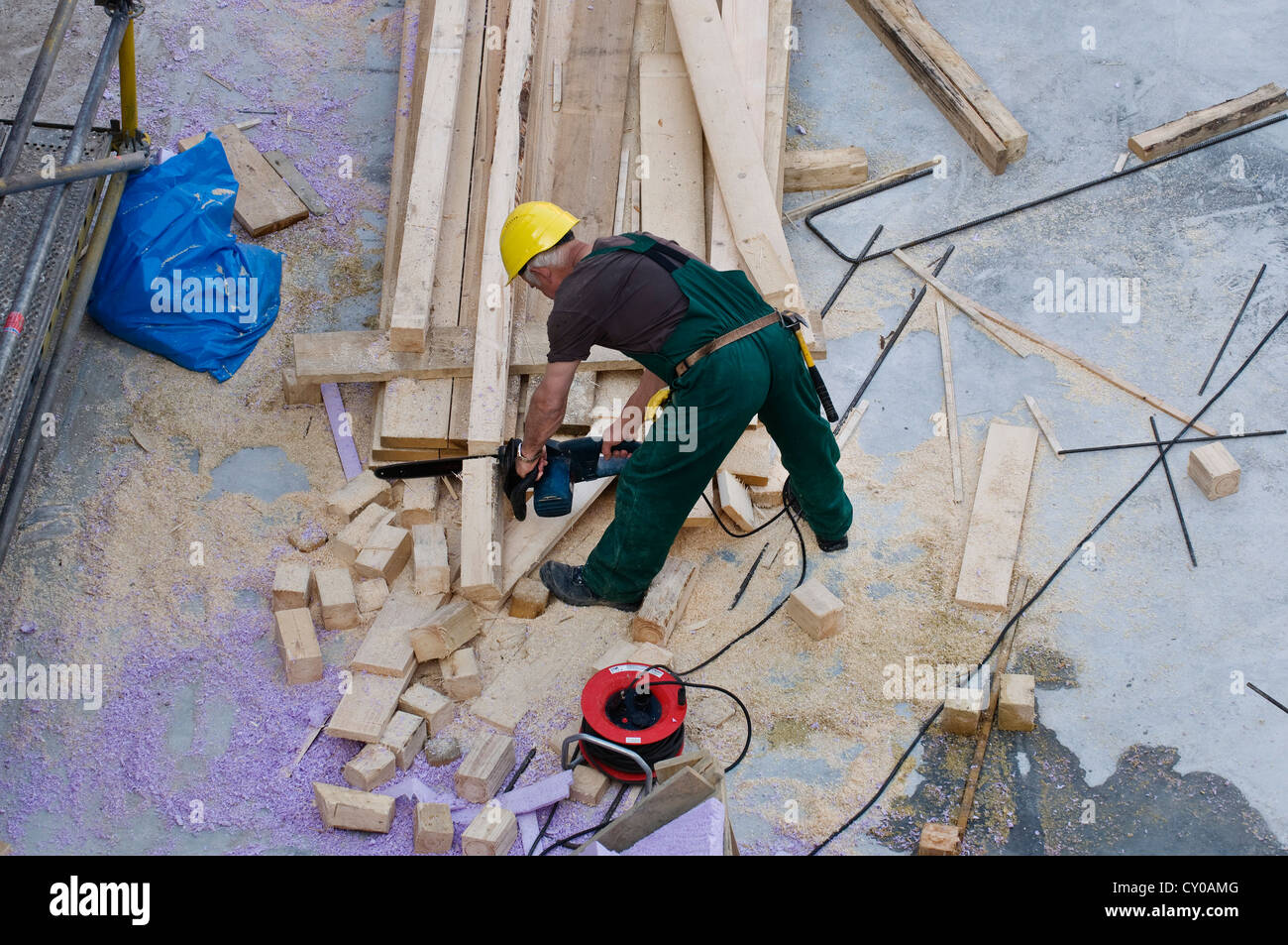 Construction worker cutting blocks of wood for boarding with a chainsaw, bird's eye perspective, PublicGround - Stock Image