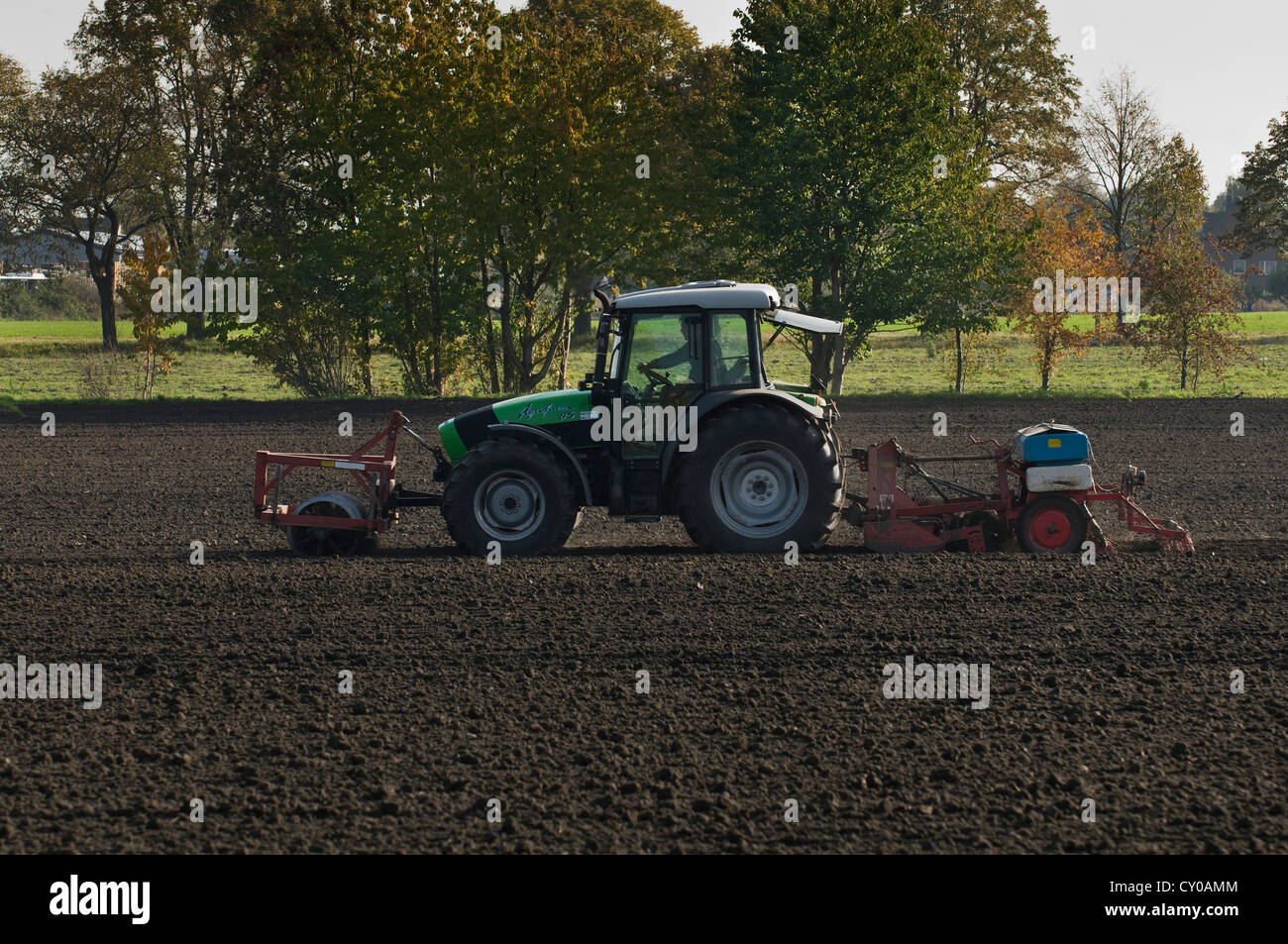 Tractor with front roller and a sowing machine at the back on a field, North Rhine-Westphalia, PublicGround - Stock Image