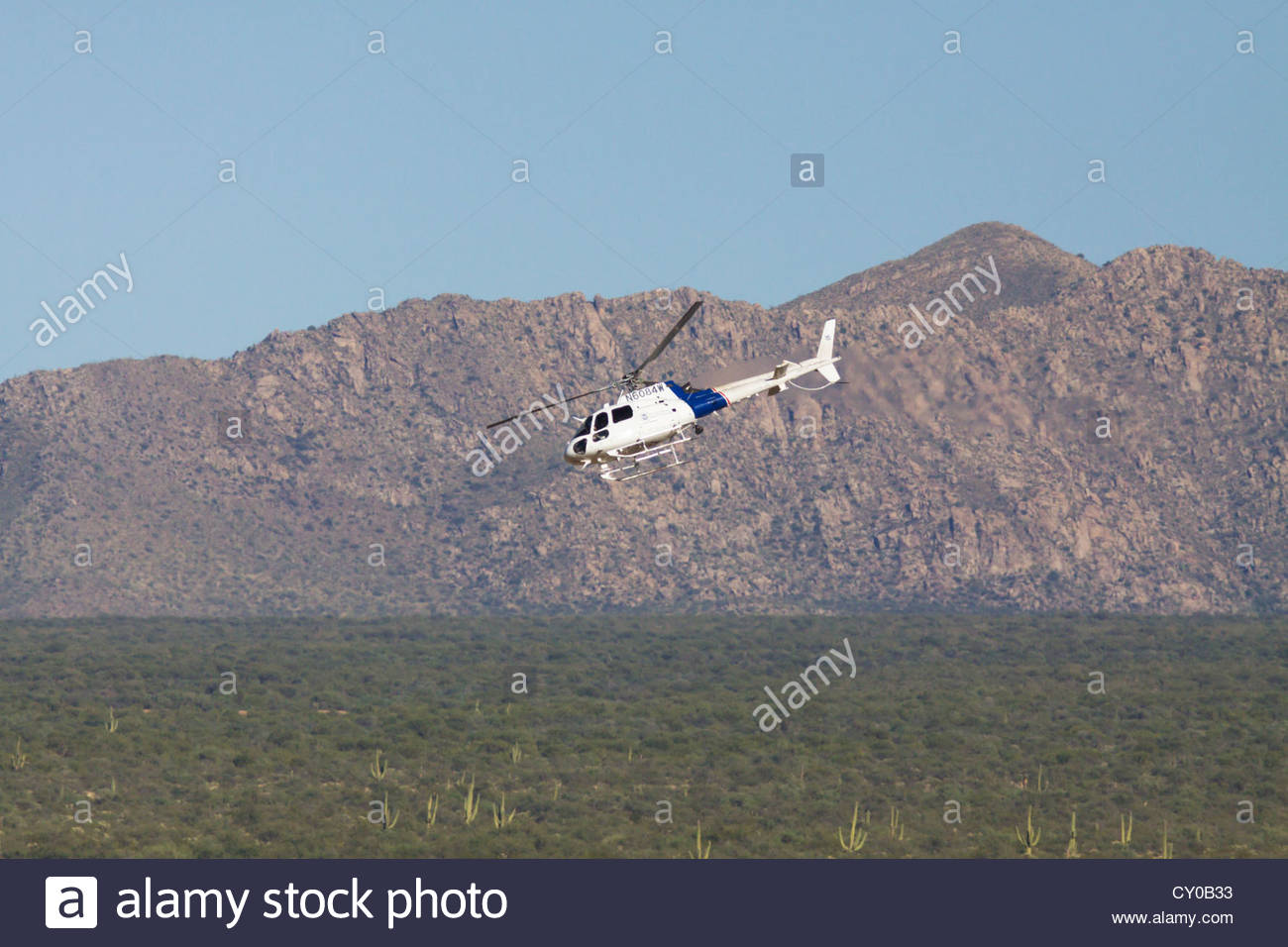 Helicopter flying over Arizona desert U S Immigration and Customs Enforcement Border Patrol searching - Stock Image