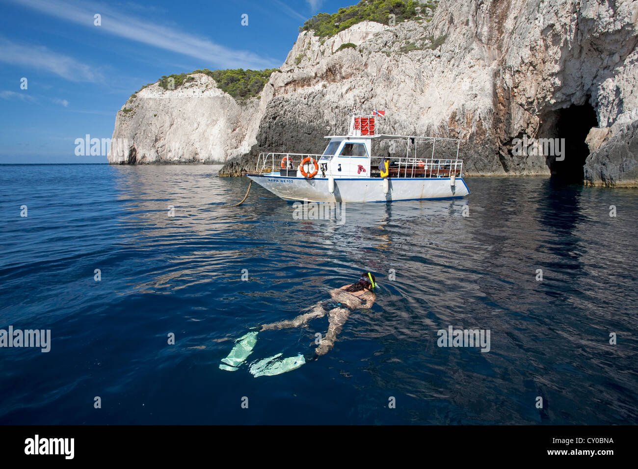 Woman snorkelling off the rocky coast, dive boat anchored in front of a grotto, rocky coast at Limni Keriou - Stock Image