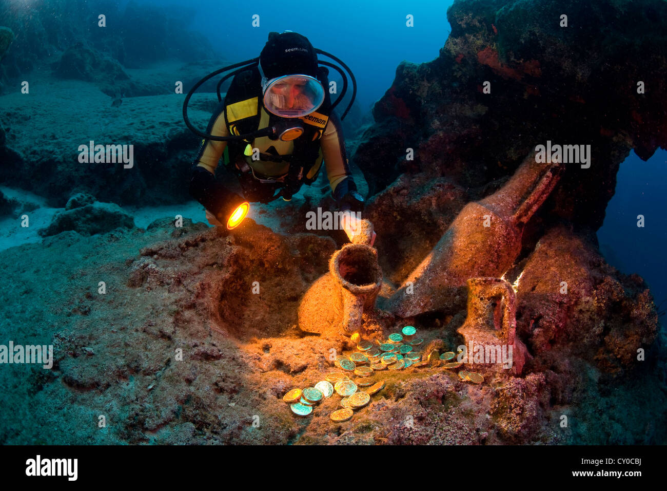 Diver discovering gold coins on the ocean floor inside old Italian amphoras dating from the 2nd century BC, Turkey - Stock Image