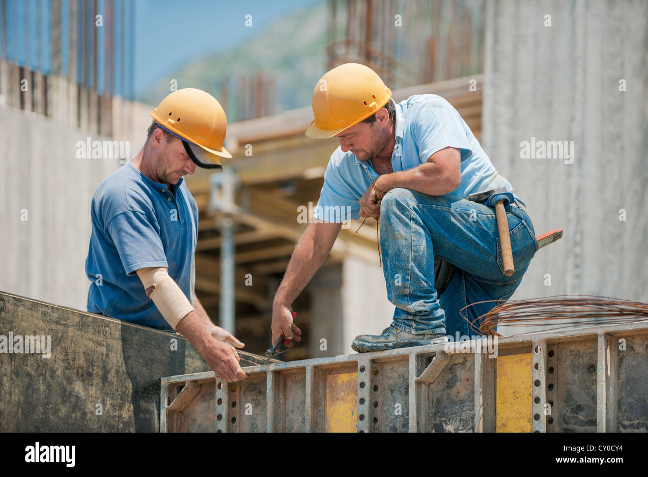 Two construction workers binding concrete formwork frames - Stock Image