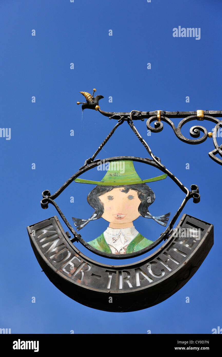 Wrought iron hanging sign for a children's traditional costume shop, Universitaetsplatz square, Salzburg, Austria, - Stock Image