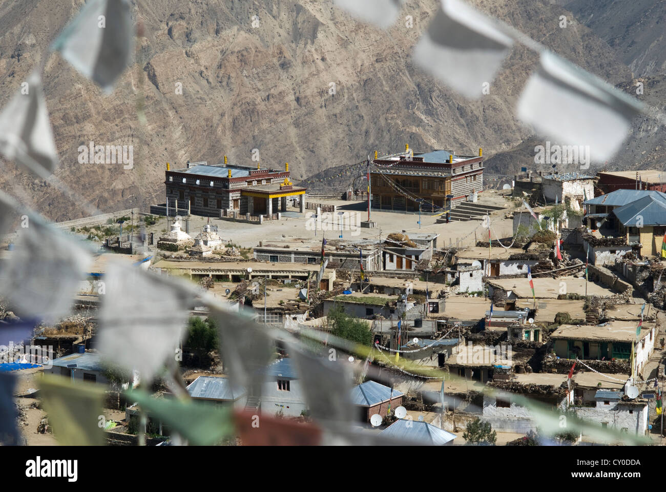 Prayerflags from a hilltop shrine frame Nako Monastery in the Kinnaur district of Northern India - Stock Image