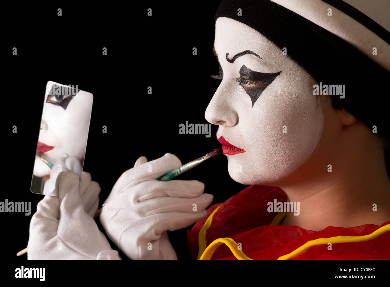 Mime performer applying Pierrot face paint with a brush - Stock Image