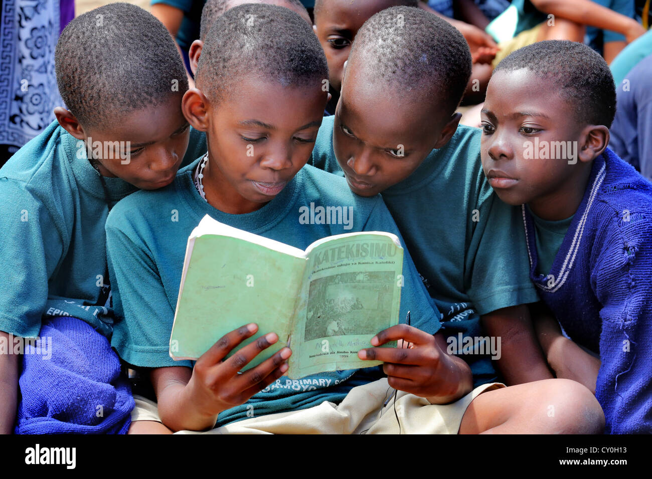 Pupils during the catholic religious education read in a catechesis book. Bagamoyo, Tansania - Stock Image