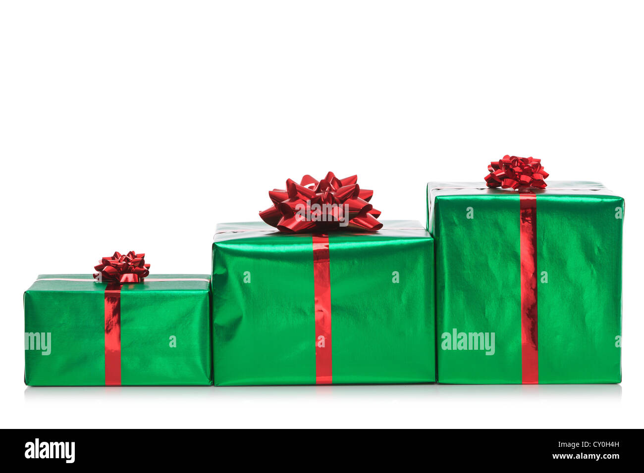 Three gift wrapped presents in green wrapping paper with red bow and ribbon, isolated on a white background. - Stock Image