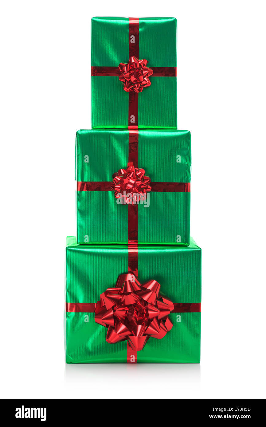 Three gift wrapped presents in green wrapping paper with red bow and three gift wrapped presents in green wrapping paper with red bow and ribbon isolated on a white background negle Images