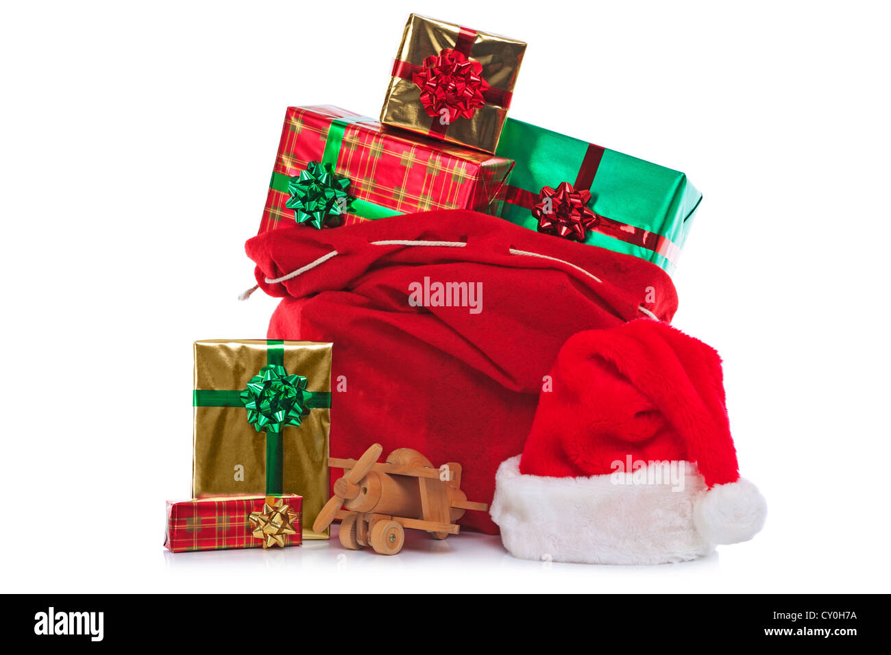 Photo of a red Santa Claus hat and sack full of gift wrapped presents and toys, isolated on a white background. - Stock Image