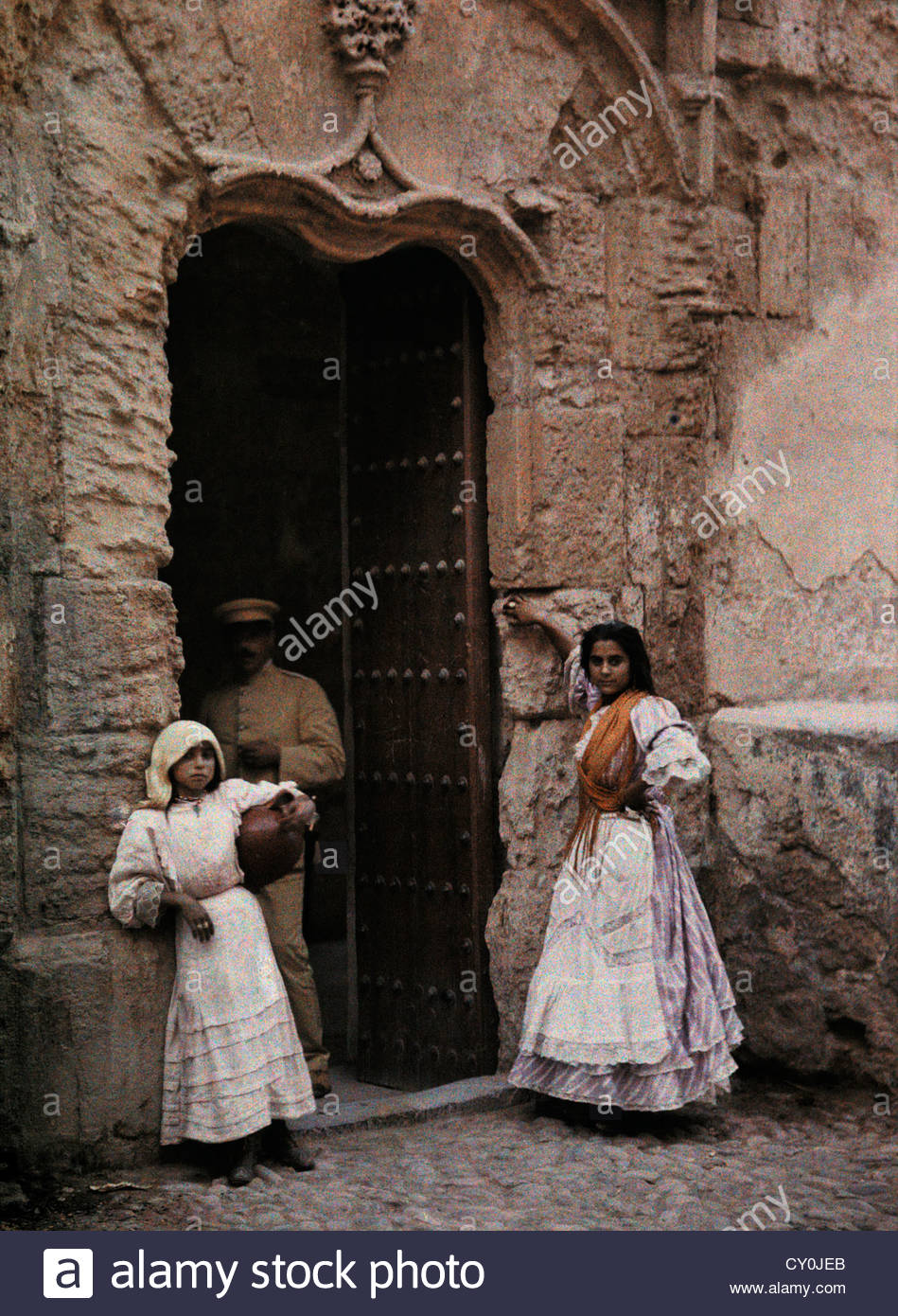 Two girls wait at a church door in Toledo. - Stock Image