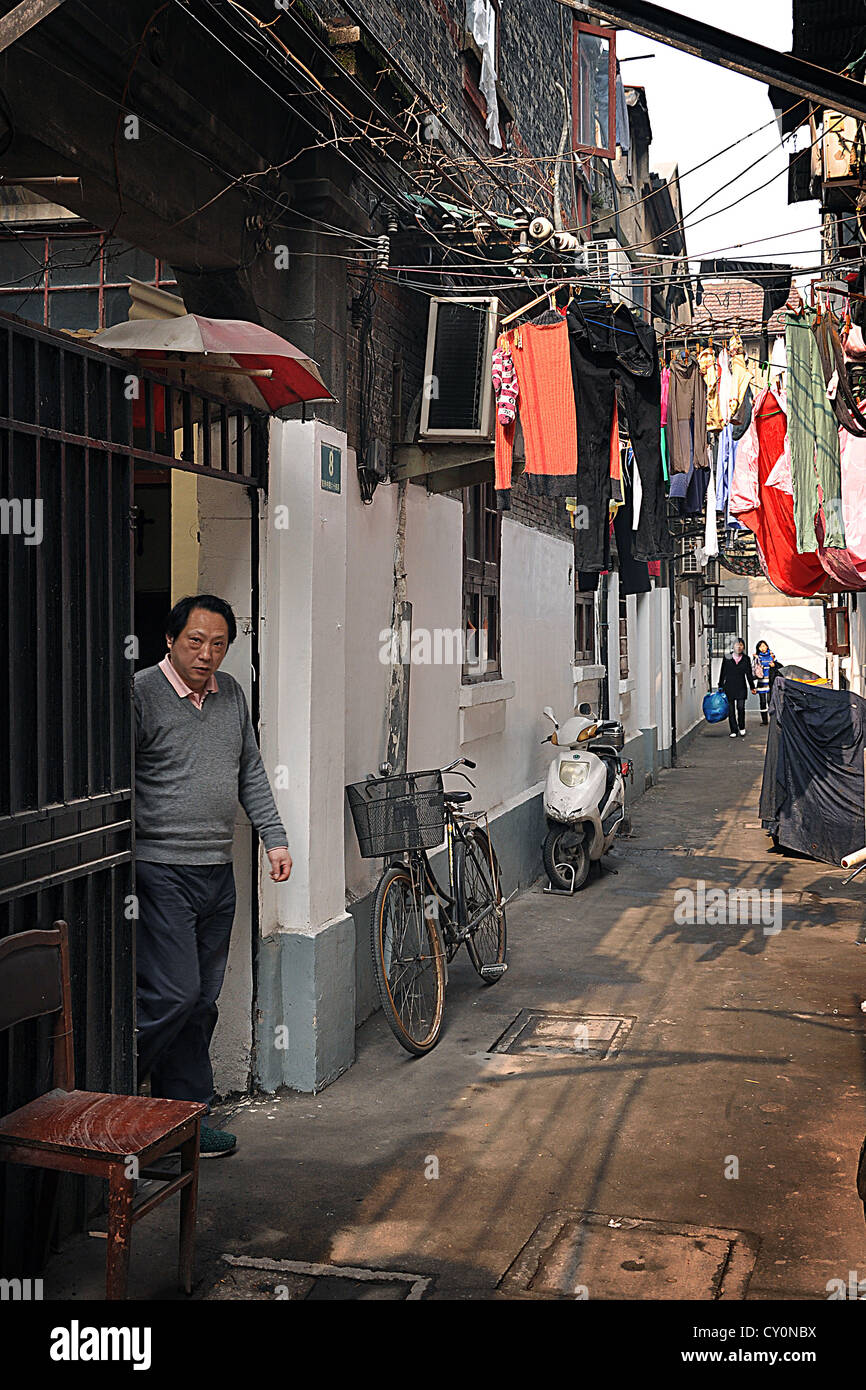 Chinese man in a lilong (traditional housing of Shanghai, equivalent of hutong in Beijing) with laundry hanging - Stock Image
