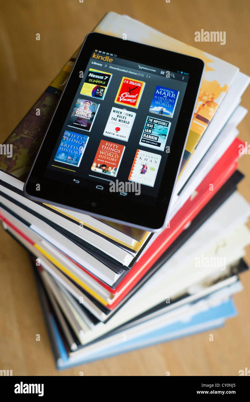 Google Nexus 7 tablet computer with kindle e-book library application and pile of traditional hardback paper books - Stock Image