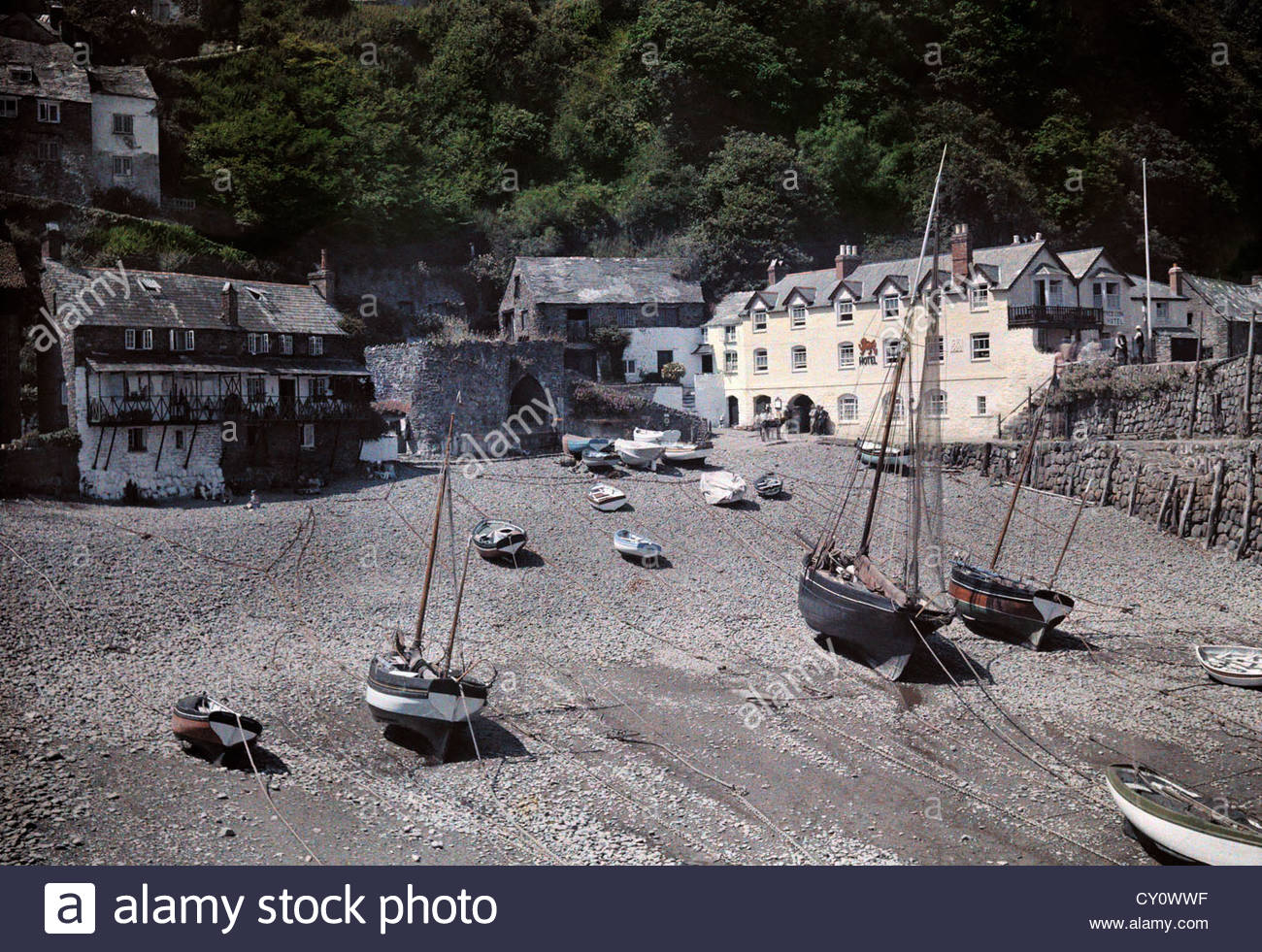 Boats rest on a rocky shore in front historic houses and inns. - Stock Image